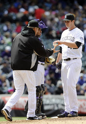 photo -   Colorado Rockies starting pitcher Drew Pomeranz hands the ball over to Colorado Rockies manager Jim Tracy in the fifth inning of a baseball game against the Arizona Diamondbacks on Sunday, April 15, 2012 in Denver. The Diamondbacks won 5-2. Colorado Rockies catcher Wilin Rosario is at center. (AP Photo/Chris Schneider)
