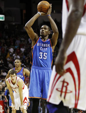 Photo - Oklahoma City Thunder forward Kevin Durant (35) hits his second of two free throws during the fourth quarter of an NBA basketball game against the Houston Rockets, Saturday, Jan. 7, 2012, in Houston. The Thunder won 98-95. (AP Photo/Eric Kayne) ORG XMIT: TXELK116