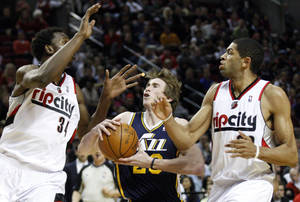 Photo -   Utah Jazz's Gordon Hayward, center, drives to the basket as Portland Trail Blazers' Hasheem Thabeet (34) and Nicolas Batum, right, defend during the first quarter of an NBA basketball game Wednesday, April 18, 2012, in Portland, Ore. (AP Photo/Rick Bowmer)