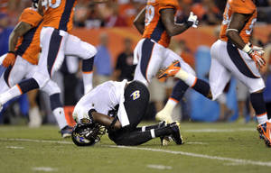 Photo - Baltimore Ravens wide receiver Jacoby Jones falls after being injured during the first half of an NFL football game against the Denver Broncos, Thursday, Sept. 5, 2013, in Denver. (AP Photo/Jack Dempsey)