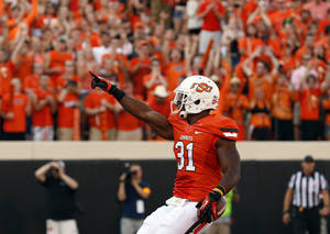 Photo - CELEBRATION: Oklahoma State's Jeremy Smith (31) celebrates a touchdown during a college football game between Oklahoma State University (OSU) and Savannah State University at Boone Pickens Stadium in Stillwater, Okla., Saturday, Sept. 1, 2012. Photo by Sarah Phipps, The Oklahoman
