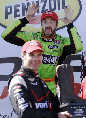 Photo - Third place finisher James Hinchcliffe, rear, of Canada, makes a face as winner Will Power, front, of Australia, is presented the winners trophy during the second IndyCar Grand Prix of Houston auto race, Sunday, Oct. 6, 2013, in Houston. (AP Photo/David J. Phillip)