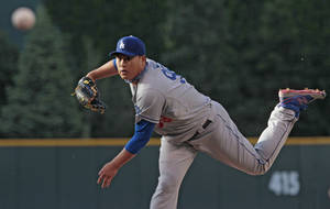 Photo - Los Angeles Dodgers starting pitcher Hyun-Jin Ryu (99) delivers a pitch against the Colorado Rockies in the  first inning of a baseball game in Denver on Friday, June 6, 2014. (AP Photo/Joe Mahoney)