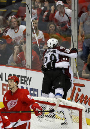 Photo - Colorado Avalanche's Nathan MacKinnon  (29) lands in the arms of Colorado Avalanche's Andre Benoit (61) after Benoit's game winning goal during overtime of an NHL hockey game against the Detroit Red Wings Thursday, March 6, 2014, in Detroit. MacKinnon assisted on the goal that defeated the Red Wings 3-2. (AP Photo/Duane Burleson)