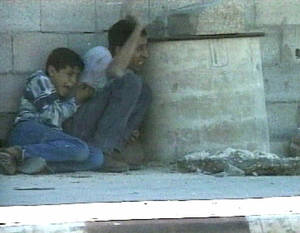 Photo - **  FILE  ** In this Sept. 30, 2000 file image from television, Jamal al-sutra signals his position while protecting his 12-year-old son Mohammed al-Dura, as they shelter behind a barrel from crossfire near Netzarim Jewish settlement in the southern Gaza Strip. More than a dozen years later, the death of a Palestinian boy allegedly shot by Israeli troops in Gaza continues to stir emotions on both sides of the conflict. A new Israeli report that tries to debunk the Palestinian narrative of the incident shows no signs of ending the saga, which for Palestinians has became a symbol of Israeli oppression and for Israel is a nasty smear campaign aimed at demonizing it. (AP Photo/France 2, Fille)  **  NO SALES TV OUT ***FRANCE OUT ***