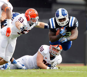 Photo -   Duke running back Juwan Thompson (23) dives for yardage against Virginia defenders Steve Greer (53) and Jake Snyder (90) during the first quarter of an ACC college football in Durham N.C., on Saturday, Oct. 6, 2012. (AP Photo/The News & Observer, Chris Seward)