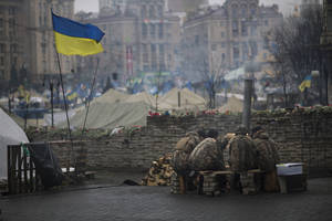 "Photo - Anti-Yanukovych protesters warm themselves next to a fire in Kiev's Independence Square, Ukraine, Wednesday, March 5, 2014. Stepping back from the brink of war, Vladimir Putin talked tough but cooled tensions in the Ukraine crisis Tuesday, saying Russia has no intention ""to fight the Ukrainian people"" but reserves the right to use force. As the Russian president held court in his personal residence, U.S. Secretary of State John Kerry met with Kiev's fledgling government and urged Putin to stand down. (AP Photo/Emilio Morenatti)"