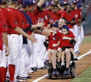 "Photo - Oklahoma City police officer Chad Peery and sons McKade, 6, left, and Morgan, 4, are greeted by members of the Oklahoma City RedHawks as Peery rolls down the third-base line in his wheelchair while rounding the bases after the third inning as part of the ""Home Run for Life"" promotion during the minor league baseball game between the Oklahoma City RedHawks and the Iowa Cubs at RedHawks Field at Bricktown in Oklahoma City, Saturday, Aug. 27, 2011. Peery was left paralyzed after being beaten while trying to break up a fight at bar earlier this year. Photo by Nate Billings, The Oklahoman ORG XMIT: KOD"