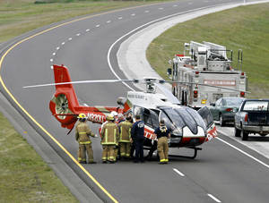 Photo - Firefighters assist a medical helicopter as a patient is loaded for transport in 2007 following an auto accident. Firefighters and paramedics are most often the ones responsible for calling a helicopter to transport a patient when an ambulance might take too long. <strong>JIM BECKEL - THE OKLAHOMAN</strong>
