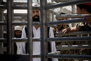 Photo - An Afghan prisoner waits in line for his release from Parwan Detention Facility after the U.S. military gave control of its last detention facility to Afghan authorities in Bagram, outside Kabul, Afghanistan, Monday, March 25, 2013. The handover of Parwan Detention Facility ends a bitter chapter in American relations with Afghanistan's mercurial president, Hamid Karzai, who demanded control of the prison as a matter of national sovereignty. (AP Photo/Anja Niedringhaus)
