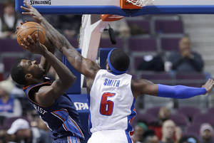 Photo - Detroit Pistons forward Josh Smith (6) reaches in and fouls Charlotte Bobcats forward Michael Kidd-Gilchrist (14) during the first quarter of an NBA basketball game in Auburn Hills, Mich., Tuesday, Feb. 18, 2014. (AP Photo/Carlos Osorio)