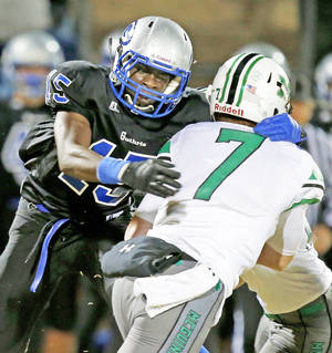Photo - Guthrie's L'Liott Curry, left, brings down Bishop McGuinness' Jacob Lewis during a game in Guthrie. Photo by Bryan Terry, The Oklahoman