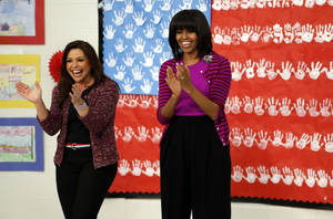 "photo - First lady Michelle Obama and Food Network chef Rachel Ray greet students at a ""Let's Move!"" program at the Eastside and Northside Elementary Schools in Clinton, Miss., Wednesday, Feb. 27, 2013. Obama and Ray visited with the children and conducted a cooking contest between the schools chefs. (AP Photo/Rogelio V. Solis)"