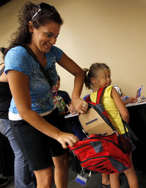 Photo - Vitoria Vaculin puts school supplies into the backpack of her daughter, Isabell Vaculin, 5.