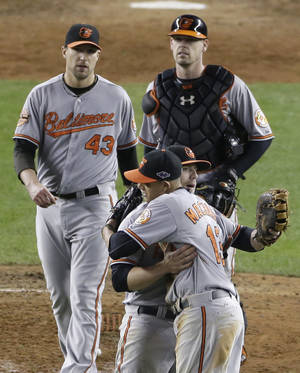 Photo -   Baltimore Orioles' Mark Reynolds and Manny Machado embrace as teammates Jim Johnson, left, and Matt Wieters approach after the Orioles defeated the New York Yankees 2-1 in Game 4 of the American League division baseball series Thursday, Oct. 11, 2012, in New York. (AP Photo/Peter Morgan)