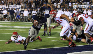Photo -   Utah State running back Kerwynn Williams (25) scores as Utah defensive end Nate Fakahafua (8) looks on in overtime during an NCCA football game Friday, Sept. 7, 2012, in Logan, Utah. Utah State defeated Utah 27-20. (AP Photo/Rick Bowmer)