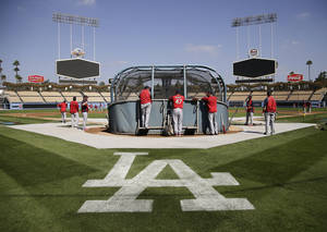 Photo - A logo for the Los Angeles Dodgers is painted on the field as the St. Louis Cardinals practice in preparation for Monday's Game 3 of the National League baseball championship series against the Dodgers, on Sunday, Oct. 13, 2013, in Los Angeles. (AP Photo/Jae C. Hong)