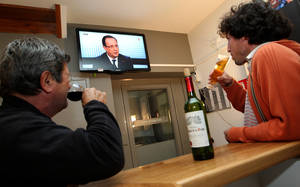 Photo - French people watch a live broadcast television debate with French President Francois Hollande, in a bar in a village of La Bastide Clairence, southwestern France, Thursday, March 28, 2013. (AP Photo/Bob Edme)