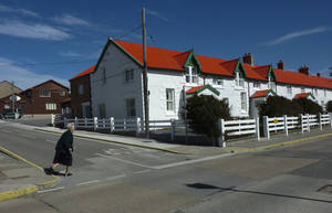 Photo -   In this March 6, 2012 photo, Daisy Rowlands crosses a street in Stanley, Falkland Islands. Rowlands' great-great grandfather James Watson was one of the earliest British settlers of the Falklands, arriving in 1839. Census results show zero population growth in the Falkland Islands. A survey in April found just 2,563 residents, a term that excludes civilian contractors and British military personnel. That's basically the same population as six years ago. (AP Photo/Michael Warren)