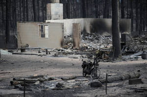 Photo - The remains of a motorcycle stands among the ruins of a home along Holmes Road Thursday, June 13, 2013, during the third day of the Black Forest Fire north of Colorado Springs, Colo. (AP Photo/The Gazette, Christian Murdock) MAGS OUT