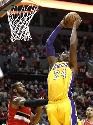 Photo -   Los Angeles Lakers guard Kobe Bryant, right, goes to the basket over Portland Trail Blazers forward LaMarcus Aldridge during the first quarter of an NBA basketball game in Portland, Ore., Wednesday, Oct. 31, 2012. (AP Photo/Don Ryan)