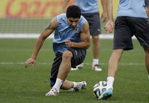 Photo - Uruguay national soccer team player Luis Suarez tries to get possession of the ball during a practice drill in a squad training session for the 2014 soccer World Cup at Itaquerao Stadium in Sao Paulo, Brazil, Wednesday, June 18, 2014.  Uruguay play England in group D of the 2014 soccer World Cup at the stadium on Thursday.  (AP Photo/Matt Dunham)