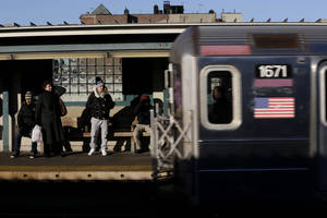 Photo - Commuters watch as a train enters the 40th St-Lowry St Station, where a man was killed after being pushed onto the subway tracks, in the Queens section of New York, Friday, Dec. 28, 2012. Police are searching for a woman suspected of pushing the man and released surveillance video Friday of her running away from the station.(AP Photo/Seth Wenig)