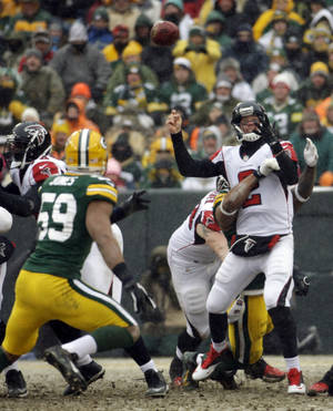 Photo - Atlanta Falcons' Matt Ryan fumbles as he is hit during the second half of an NFL football game against the Green Bay Packers Sunday, Dec. 8, 2013, in Green Bay, Wis. The Packers recovered the fumble. (AP Photo/Morry Gash)