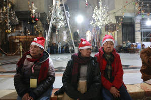 Photo - Christian worshippers visit the Church of Nativity, traditionally believed by Christians to be the birthplace of Jesus Christ, in the West Bank town of Bethlehem on Christmas Eve, Tuesday, Dec. 24, 2013. (AP Photo/Majdi Mohammed)