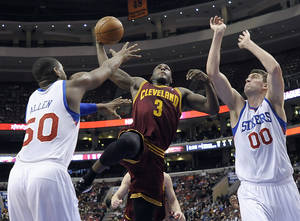 Photo - Cleveland Cavaliers' Dion Waiters (3) goes up for a dunk over Philadelphia 76ers' Lavoy Allen (50) and Spencer Hawes (00) during the first half of an NBA basketball game, Tuesday, Feb. 18, 2014, in Philadelphia. (AP Photo/Michael Perez)