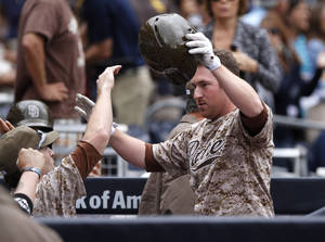 Photo - San Diego Padres' Jedd Gyorko celebrates with teammates  after his solo home run in the first inning of an MLB baseball game against Detroit Tigers Sunday, April 13, 2014, in San Diego. (AP Photo/Don Boomer)