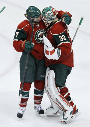 Photo - Minnesota Wild center Matt Cullen, left, congratulates Minnesota Wild goalie Niklas Backstrom (32), of Finland, after the Wild beat the Los Angeles Kings 2-1 in an NHL hockey game in St. Paul, Minn., Tuesday, April 23, 2013.(AP Photo/Ann Heisenfelt)