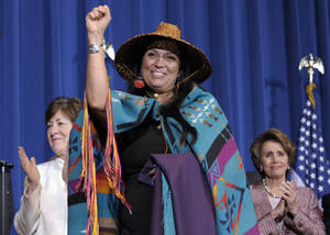 Photo - Deborah Parker, vice chairwoman of the Tulalip Tribes of Washington State, center, flanked by Sen. Susan Collins, R-Maine, left, and House Minority Leader Nancy Pelosi of Calif., gestures before President Barack Obama before he signed the Violence Against Women Act, Thursday, March 7, 2013, at the Interior Department in Washington. (AP Photo/Susan Walsh)