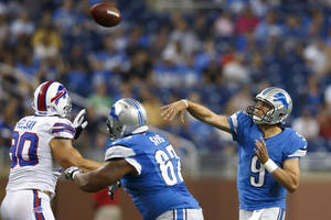 Photo -   Detroit Lions quarterback Matthew Stafford (9) passes the ball as guard Rob Sims (67) blocks Buffalo Bills defensive end Chris Kelsay (90) during the first quarter of an NFL preseason football game in Detroit, Thursday, Aug. 30, 2012. (AP Photo/Rick Osentoski)