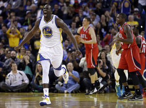 Photo - Golden State Warriors' Draymond Green, left, celebrates a score against the Atlanta Hawks during the second half of an NBA basketball game Friday, March 7, 2014, in Oakland, Calif. (AP Photo/Ben Margot)