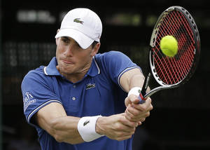 Photo - John Isner of the USA returns to opponent Ivo Karlovic of Croatia during a quarterfinal match at the Hall of Fame Tennis Championships in Newport, R.I. Friday, July 12, 2013. Isner won 7-6 (3), 7-6 (3). (AP Photo/Elise Amendola)
