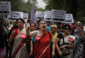"""Photo - FILE- In this Saturday, May 31, 2014 file photograph, members of the All India Democratic Women's Association (AIDWA) shout slogans during a protest against the gang rape of two teenage girls, in New Delhi, India. Beyond highlighting the rampant sexual violence in India, last week's horrific crime is drawing attention to a glaring and fundamental problem across the country that threatens women's safety: the lack of toilets.   The placard reads 'Arrest all accused in the gang rape."""" (AP Photo/Altaf Qadri, file)"""