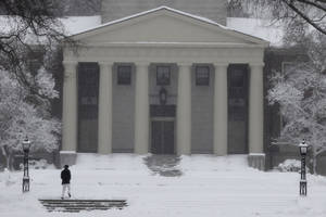 Photo - A woman walks through a snowstorm on the campus of Phillips Academy in Andover, Mass. Tuesday, March 19, 2013. (AP Photo/Winslow Townson)