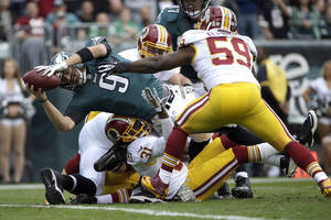 Photo - Philadelphia Eagles quarterback Nick Foles (9) dives into the end zone for a touchdown as Washington Redskins inside linebacker London Fletcher (59) reaches to stop him during the first half of an NFL football game in Philadelphia, Sunday, Nov. 17, 2013. (AP Photo/Matt Slocum)