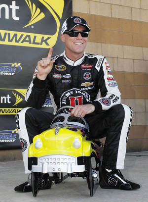 Photo - Kevin Harvick sits on a toy race car trophy following qualifying for Saturday's NASCAR Sprint Cup Series auto race at Kansas Speedway in Kansas City, Kan., Friday, May 9, 2014. Harvick won the pole position for the race. (AP Photo/Colin E. Braley)