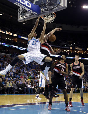 Photo - New Orleans Hornets forward Anthony Davis (23) dunks in front of Portland Trail Blazers forward Joel Freeland, guard Ronnie Price (24) and center Meyers Leonard (11) in the second half of an NBA basketball game in New Orleans, Wednesday, Feb. 13, 2013. The Hornets won 99-63. (AP Photo/Gerald Herbert)