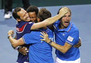 Photo - France's Gael Monfils celebrates with teammates Michael llodra, left, and Julien Benneteau, right, after winning his singles match against German player Peter Gojowczyk, in the quarterfinals of the Davis Cup in Nancy, eastern France, Sunday April 6, 2014. France qualifies for the semifinals with a 3-2 score.(AP Photo/Remy de la Mauviniere)