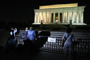 Photo - People take pictures in front of the steps of the closed Lincoln Memorial, Tuesday, Oct. 1, 2013, in Washington. The museums that draw millions of visitors to the National Mall closed their doors Tuesday, memorials were barricaded and trash will go uncollected in the nation's most-visited national park due to the first government shutdown in 17 years.  (AP Photo/Alex Brandon)