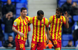 Photo - FC Barcelona's Lionel Messi, left, celebrates after scoring a penalty with teammates Neymar, right, and Daniel Alves, center, during a Spanish La Liga soccer match against Espanyol at Cornella-El Prat stadium in Cornella Llobregat, Spain, Saturday, March 29, 2014. (AP Photo/Manu Fernandez)