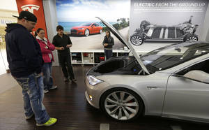 Photo - FILE - In this March 17, 2014 file photo, Robert and Sarah Reynolds, left, check out a new Tesla all electric car with Tesla representatives John Van Cleave and Raven Rivera, right, at a Tesla showroom inside the Kenwood Towne Centre in Cincinnati. The Commerce Department releases durable goods for May on Wednesday, June 25, 2014. (AP Photo/Al Behrman)