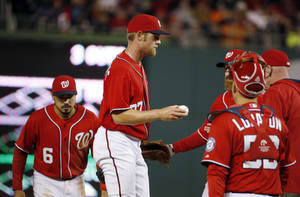Photo - Washington Nationals starting pitcher Stephen Strasburg (37) holds the ball out to manager Matt Williams as he is taken out of the baseball game during the fifth inning against the Atlanta Braves at Nationals Park on Saturday, April 5, 2014, in Washington. The Braves won 6-2. (AP Photo/Alex Brandon)