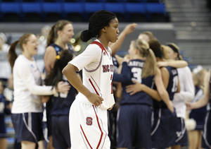Photo - North Carolina State's Len'Nique Brown walks off the court as BYU players celebrate the team's 72-57 win in a first-round game in the NCAA women's college basketball tournament on Saturday, March 22, 2014, in Los Angeles. (AP Photo/Jae C. Hong)