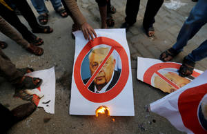 Photo - Palestinians stand over pictures of the former Israeli Prime Minister Ariel Sharon as another holds a burning poster of him in Khan Younis, southern Gaza Strip, Saturday, Jan. 11, 2014. Sharon was loathed by many Palestinians as a bitter enemy who did his utmost to sabotage their independence hopes — by leading military offensives against them in Lebanon, the West Bank and Gaza and a settlement drive on the lands they want for a state. Sharon died Saturday, eight years after a debilitating stroke put him into a coma. He was 85. (AP Photo/Hatem Moussa)