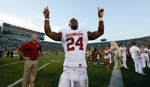 Photo - CELEBRATION: Oklahoma's Brennan Clay (24) celebrates in front of fans after a college football game between the University of Oklahoma Sooners and the Notre Dame Fighting Irish at Notre Dame Stadium in South Bend, Ind., Saturday, Sept. 28, 2013. OU won, 35-21. Photo by Nate Billings, The Oklahoman