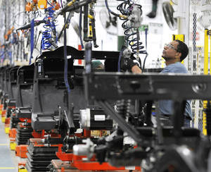 Photo - Assembler Barry Austin works July 19 on a golf car production line at the E-Z-GO plant in Augusta, Ga.  AP Photo